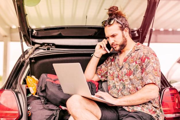 Mec avec ordinateur portable et smartphone près de la voiture Photo gratuit