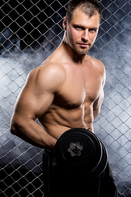 Mec puissant avec un haltères montrant les muscles sur la clôture Photo gratuit