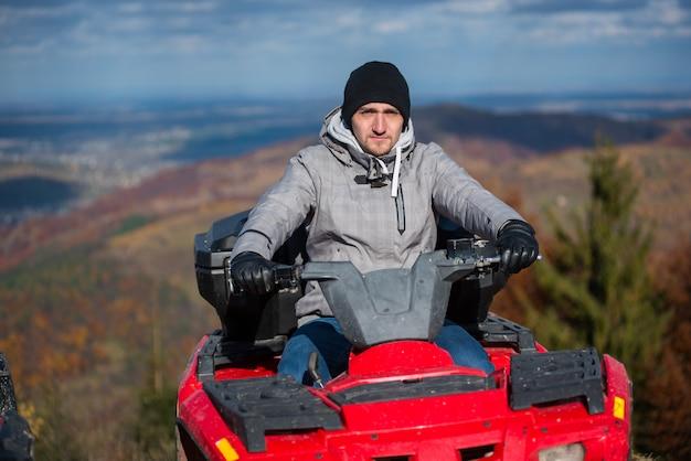 Mec en quad rouge sur la nature de l'arrière-plan flou à la journée ensoleillée Photo Premium