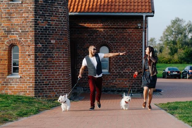 Mec avec sa petite amie courant dans la rue avec leurs animaux domestiques Photo Premium