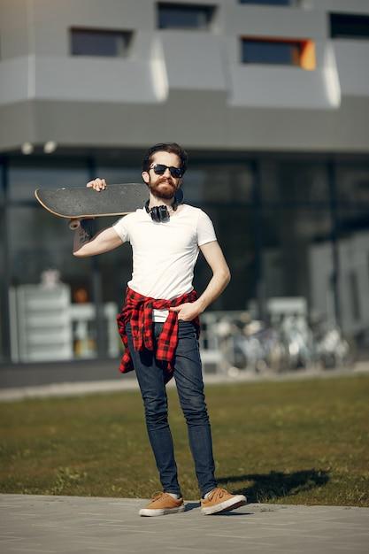 Mec avec skate dans la rue Photo gratuit