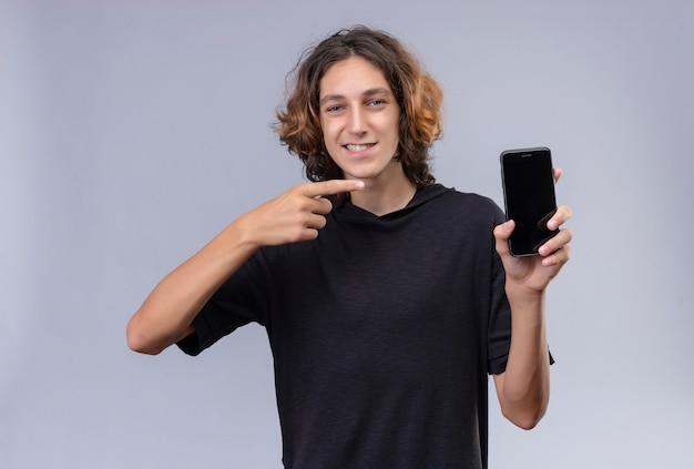 Mec Souriant Aux Cheveux Longs En T-shirt Noir Tenant Un Téléphone Et Pointer Vers Le Téléphone Sur Un Mur Blanc Photo gratuit