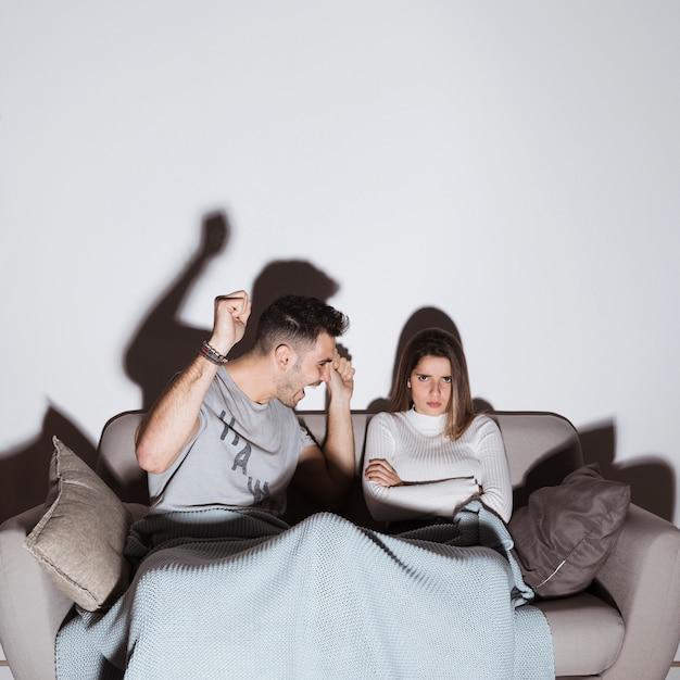 Mec souriant et dame en colère devant la télé sur un canapé Photo gratuit