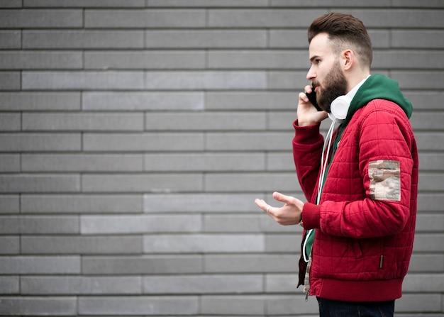 Mec, vue côté, à, écouteurs, parler, téléphone Photo gratuit