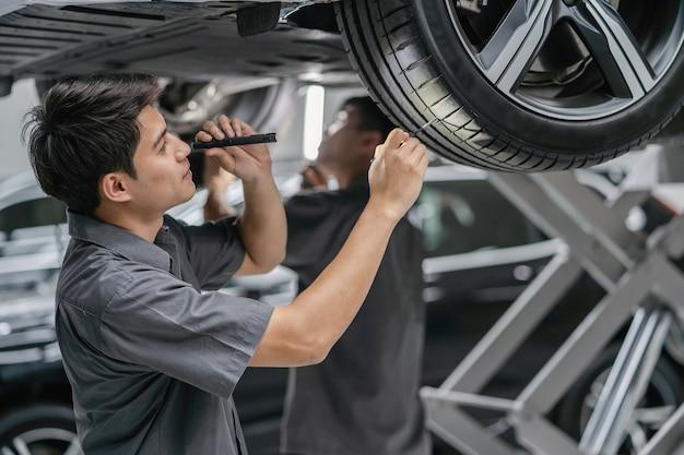 Mécanicien asiatique contrôle des pneus et du flambeau dans un centre de maintenance qui fait partie de la salle d'exposition Photo Premium