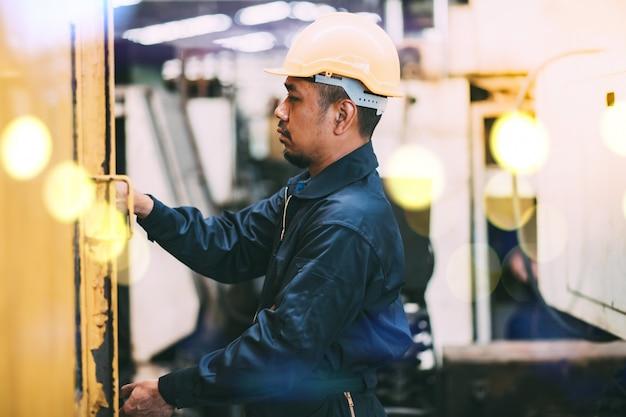 Mécanicien Asiatique D'ingénierie En Sécurité Combinaison De Mécanicien Et Casque Debout Bras Croisés Au Camion Et Au Garage D'entretien Des Chariots élévateurs. Photo Premium