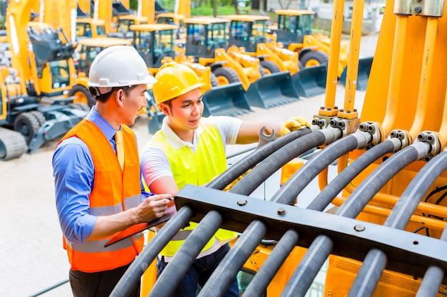 Mécanicien asiatique et ingénieur avec machine Photo Premium