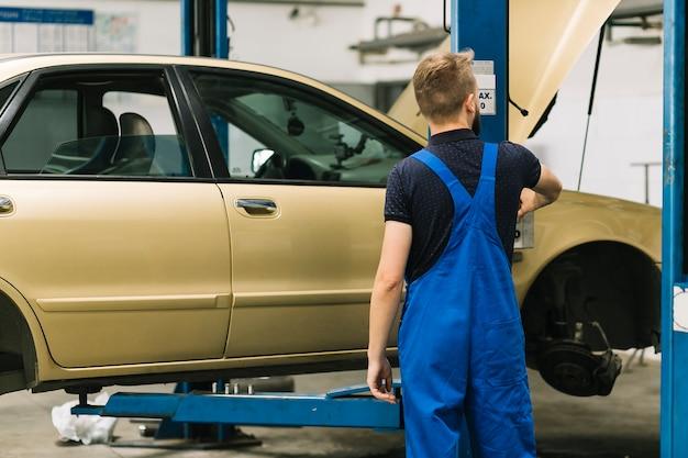 Mécanicien automobile debout près de locklift Photo gratuit