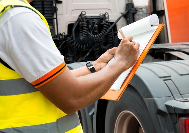 Le mécanicien automobile écrit sur le presse-papiers en inspectant un camion. Photo Premium