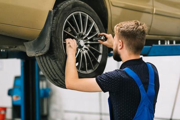 Mécanicien automobile essayant de mettre la prise dans la roue automatique Photo gratuit