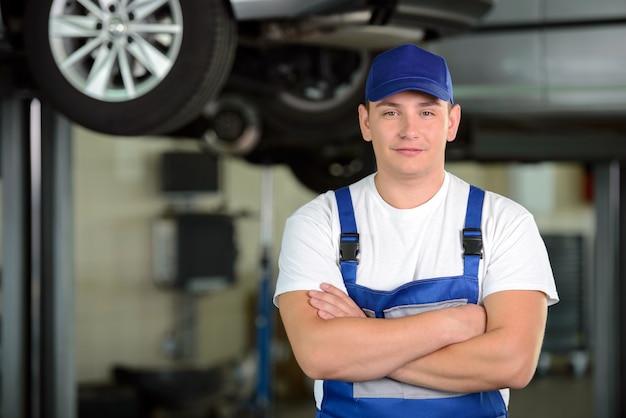 Mécanicien automobile masculin confiant dans l'atelier. Photo Premium