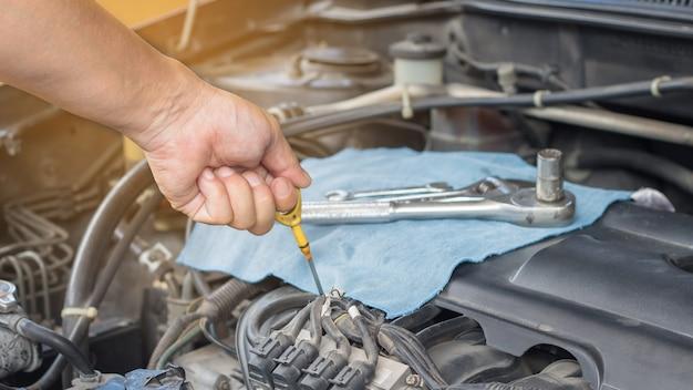 Mécanicien automobile avec outil de contrôle de fonctionnement et réparation d'un ancien moteur de voiture à la station-service Photo Premium