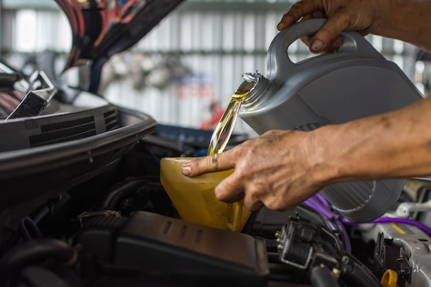 Un mécanicien automobile remplit une huile moteur lubrifiante fraîche au garage pour l'entretien d'une voiture Photo Premium