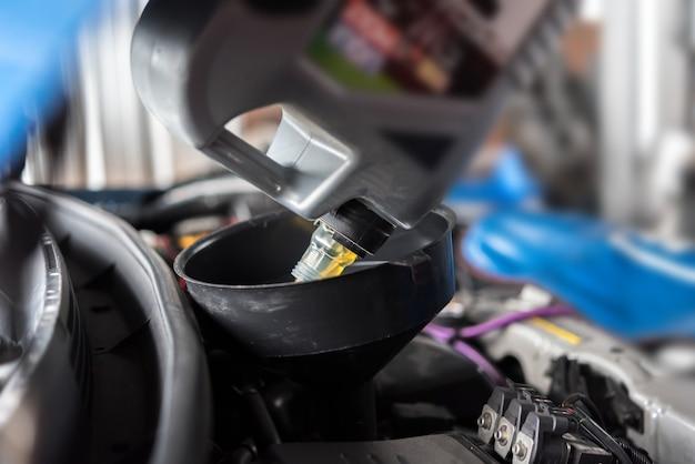 Un mécanicien automobile remplit une huile de moteur lubrifiante neuve Photo Premium