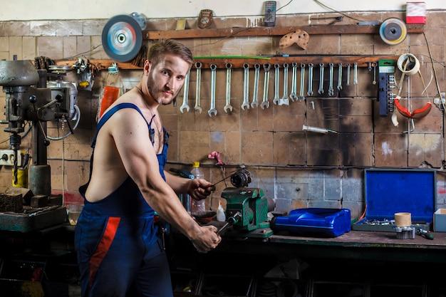 Mécanicien automobile répare un détail serré dans un étau. Photo Premium