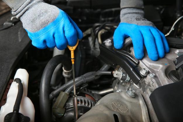 Mécanicien Automobile Tire La Jauge D'huile Du Moteur De La Voiture Photo Premium