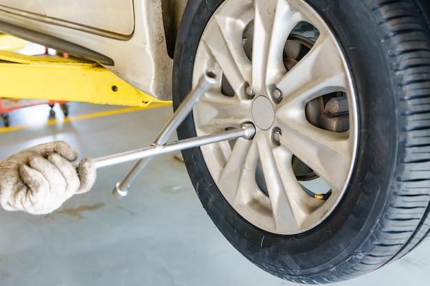 Mécanicien automobile avec tournevis électrique, changement de pneu à l'atelier Photo Premium