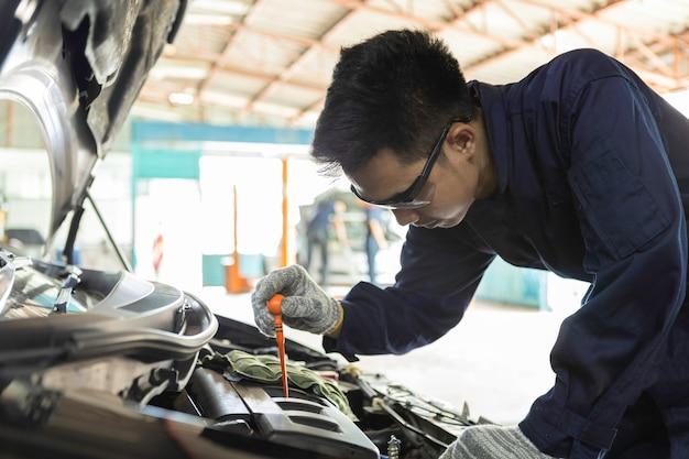 Un mécanicien automobile vérifie l'huile moteur pour l'entretien du véhicule d'entretien. Photo Premium