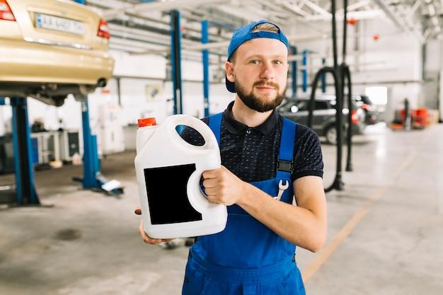 Mécanicien avec canalisation d'huile à l'atelier Photo gratuit