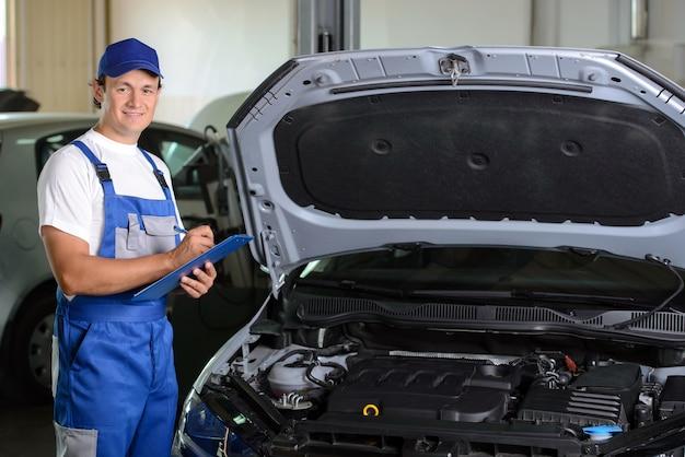 Mécanicien dans un atelier de réparation automobile debout à côté de la voiture. Photo Premium