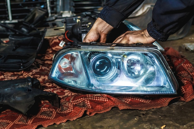 Un mécanicien dans son atelier répare un phare de voiture. concept de service de voiture. Photo Premium