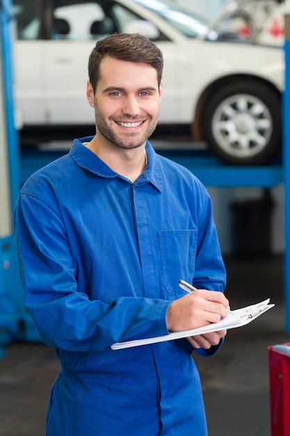 Mécanicien écrivant sur un bloc-notes au garage de réparation Photo Premium