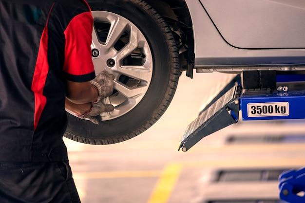 Le mécanicien est en train de changer les pneus de la voiture pour ceux qui utilisent le centre de pneu. Photo Premium