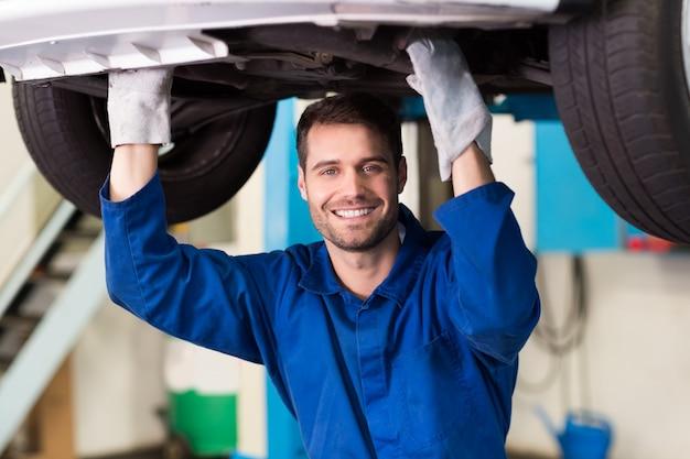 Mécanicien examinant sous la voiture Photo Premium