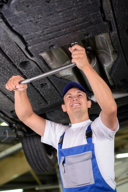Un mécanicien examine la suspension d'une voiture levée. Photo Premium