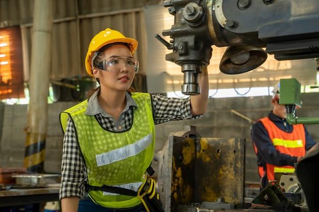 Mécanicien Féminin Travaillant Et Vérifiant La Machine En Usine. Photo Premium