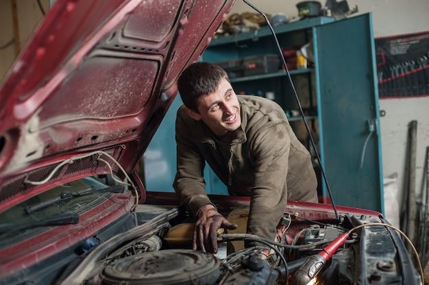 Mécanicien de service automobile travaillant dans une voiture sous le capot Photo Premium