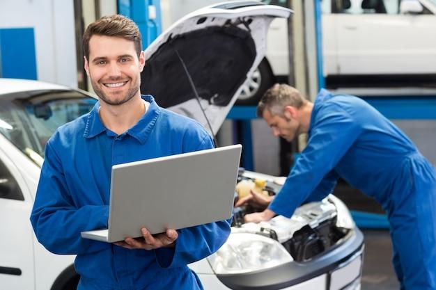 Mécanicien souriant à l'aide d'un ordinateur portable Photo Premium
