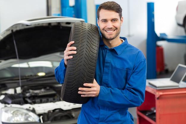 Mécanicien tenant une roue de pneu Photo Premium