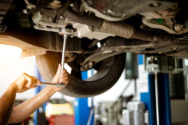 Mécanicien tourne l'écrou pour fixer la voiture dans le garage, service de réparation. Photo Premium