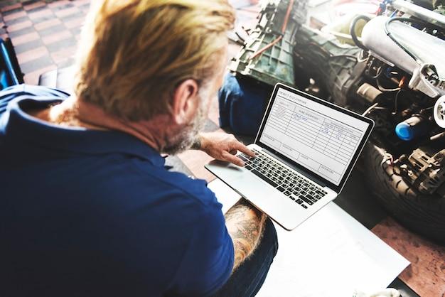 Un mécanicien travaillant avec son ordinateur portable Photo Premium