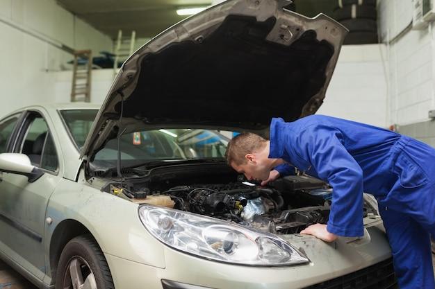 Mécanicien travaillant sous le capot de la voiture Photo Premium