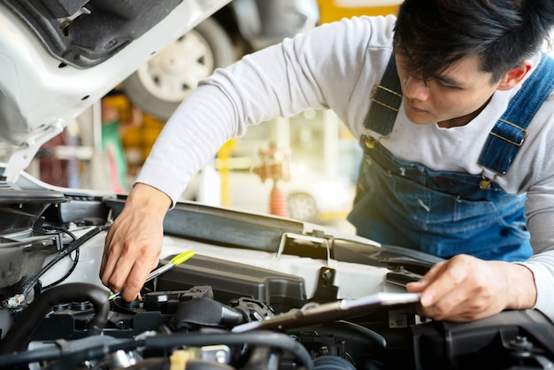 Mécanicien travaillent dans le garage. mécanicien travaillent dans le garage. service de réparation avec clip b Photo Premium