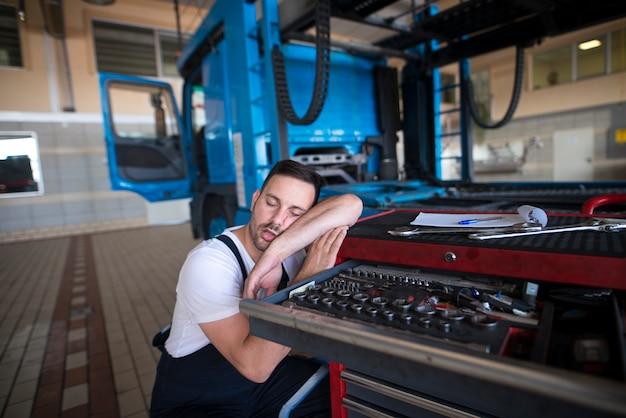 Mécanicien De Véhicule épuisé S'endormir Dans Son Atelier Photo gratuit