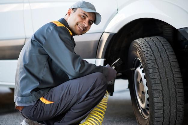 Mécanicien vérifiant la pression d'un pneu de camionnette Photo Premium
