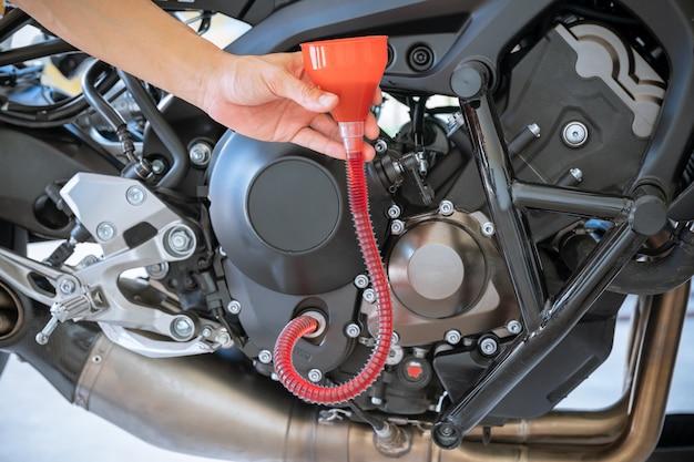 Mécanicien versant de l'huile fraîche versée lors d'un changement d'huile dans le moteur de la moto Photo Premium