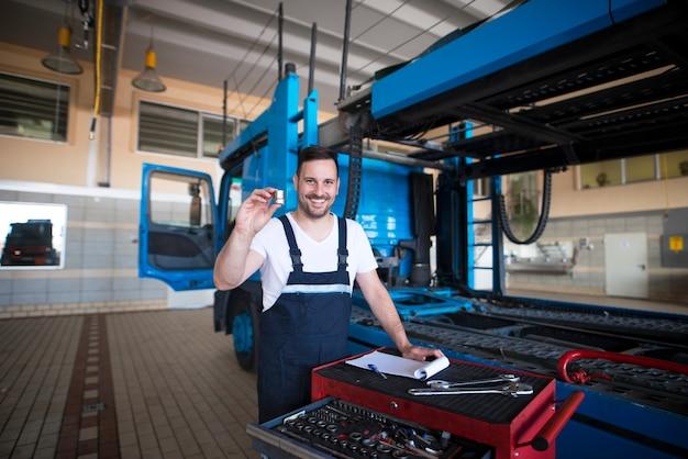 Mécaniciens De Camions D'âge Moyen Expérimentés Détenant Des Pièces Et Des Outils Dans Un Atelier De Réparation Près Du Camion Photo gratuit