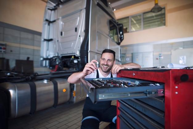 Mécaniciens De Véhicules Debout Près Du Chariot à Outils Et Choisissant L'outil Approprié Pour L'entretien Des Camions Photo gratuit