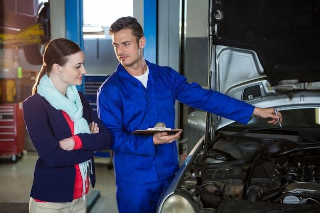 Mechanic montrant la citation à un client Photo gratuit