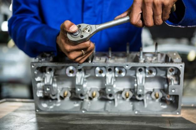 Mechanic partie moteur de réparation à cliquet dans le garage de réparation Photo gratuit