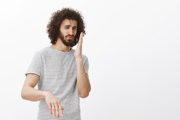 Mécontent Bel Homme Hispanique En T-shirt Rayé, Agitant La Paume Près Du Nez Et Fronçant Les Sourcils, Sentant Une Odeur Horrible Photo gratuit