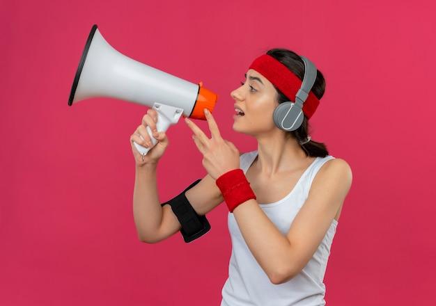 Mécontent Jeune Fille De Remise En Forme Sportswear Avec Bandeau Et écouteurs Criant Au Mégaphone Debout Sur Le Mur Rose Photo gratuit