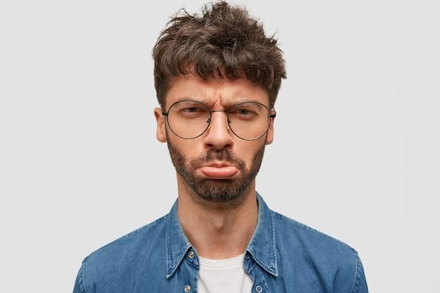 Le Mécontentement Mal Rasé Jeune Homme Serre Les Lèvres Et A Une Expression Misérable, étant Affligé Photo gratuit
