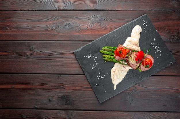 Médaillons De Veau Aux Asperges Sur Vaisselle Noire, Table En Bois Photo Premium