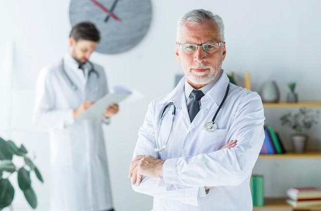 Médecin âgé confiant au bureau Photo gratuit