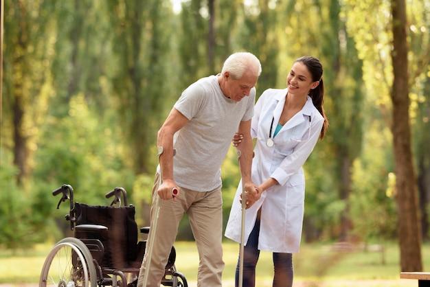 Le médecin aide le vieil homme à se tenir sur des béquilles. Photo Premium